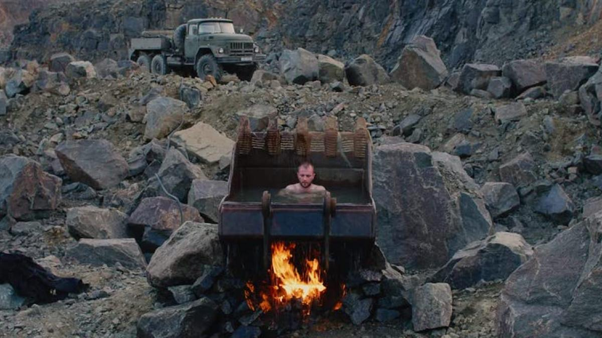 An unclothed man sits in a freestanding backhoe bucket filled with water. A fire is burning underneath the bucket. The surrounding landscape is gray, rocky, and barren. A water trucks is parked in the background.