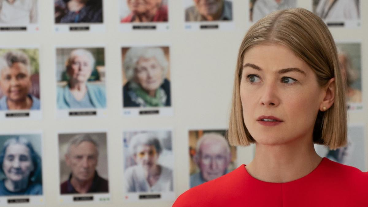 A woman with a blonde bob haircut and red shirt, standing in front of a wall of headshot photographs of elderly people.