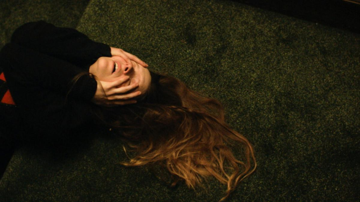 A woman in a black and red sweater lays on a green carpeted floor, her hands partly covering her face and her hair spread out on the ground.
