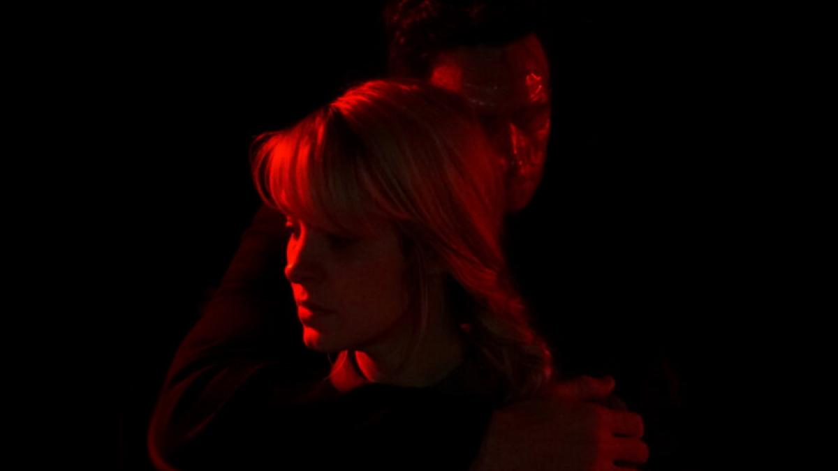 Red-and-black image of a blonde woman being held around the throat by a masked stranger.