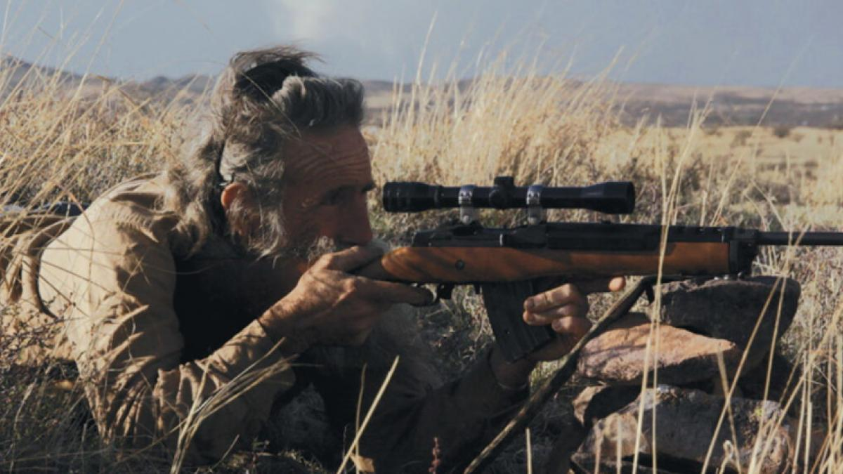 An older, bearded man laying down in a field of dry grass, pointing a rifle with a scope at something offscreen.
