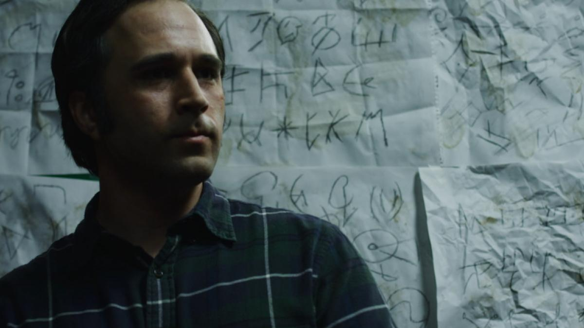 A dark-haired man standing in front of a wall covered in wrinkled sheets of paper, each with numerous scrawled symbols.