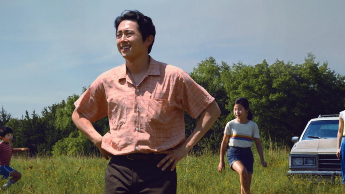 A man in a red-and-white checked shirt standing with his hands on his hips, surveying a grass field. His family -- wife, daughter, and young son -- are in the background with the family car.