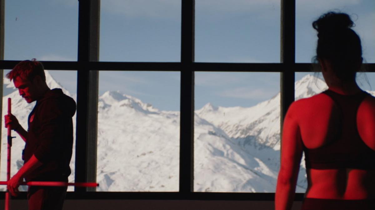 In the foreground, a woman in a sport tank with her hair in a bun, her back to the camera. In the middle ground, a bearded man in a hoodie with his back to her. In the background, windows looking out over snowy mountains.
