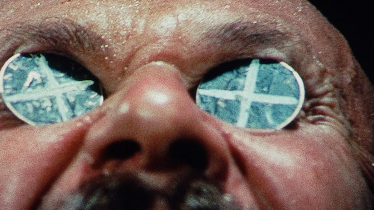 A close-up of a man's sweaty, upturned face. Two pennies painted with X's have been placed on his eyes.