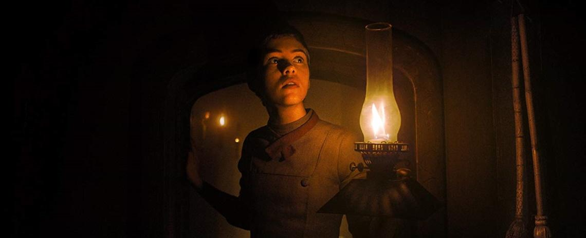 Gretel (Sophia Lillis) investigates the witch's house by lamplight in Osgood Perkins' 'Gretel & Hansel'.