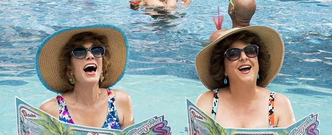 Two middle-aged women with delighted expressions, wearing swimsuits, sunhats, and sunglasses. They are floating chest-deep in a swimming pool while holding menus.